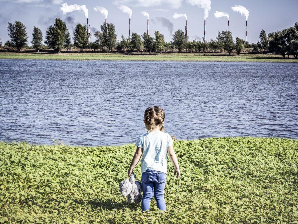 Dziewczynka patrzy na dymiące kominy.